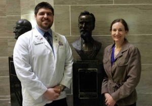 Dr. Maria Coffman and Student Doctor Justin Penny stand next to a bust of A.T. Still, M.D., D.O., the originator of osteopathy who was recently inaugurated into the Missouri Hall of Fame.